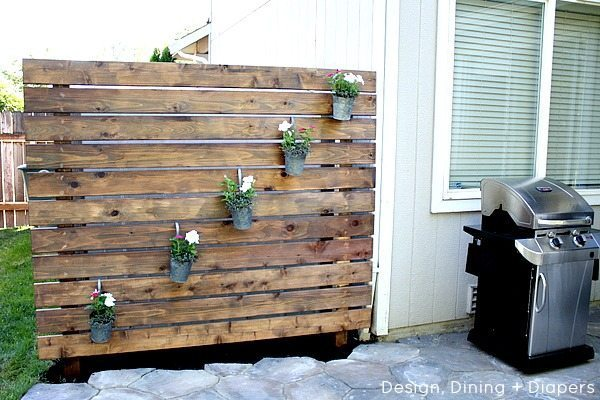 Learn how to build your own garden slat wall, a great wood privacy wall that can hide an ugly shed or make your patio more private from neighbors.