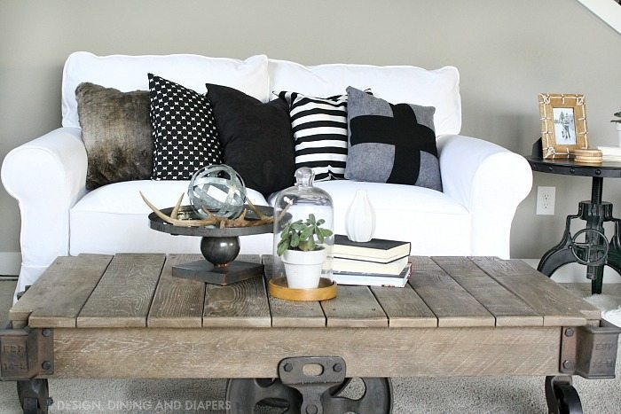 White Couch with Black and White Pillows and Rustic Coffee Table