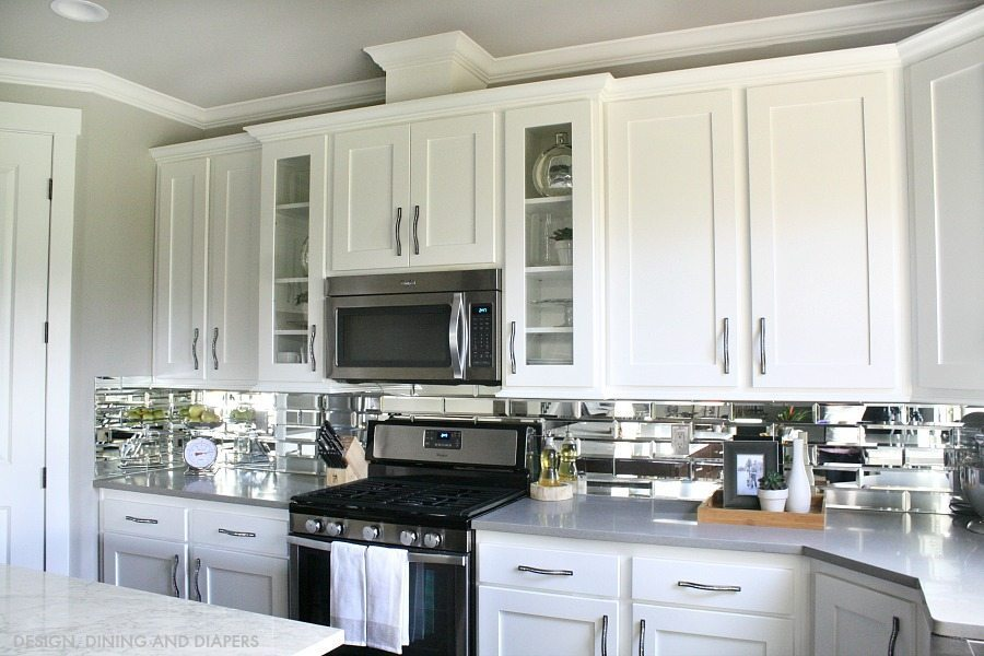 White kitchen cabinets and mirror backsplash